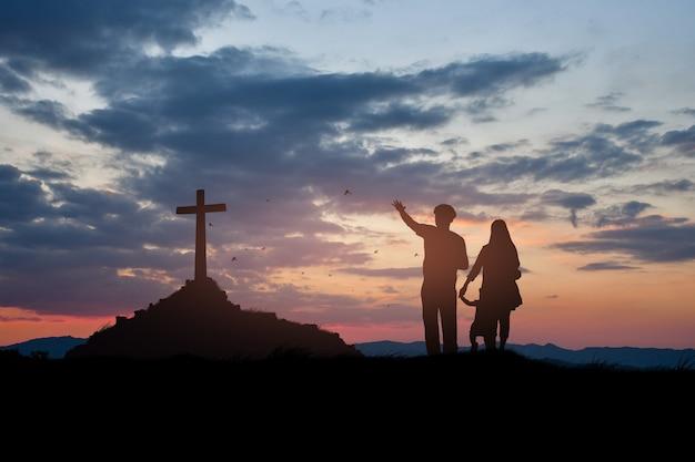 Sylwetka chrześcijańskiej rodziny stojącej z krzyżem na cześć boga