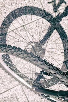 Sylwetka cienia przedniego koła roweru i widok opony na betonowej powierzchni miejskiej w pionie
