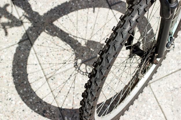 Sylwetka cienia przedniego koła roweru i widok opony na miejskim betonowym tle