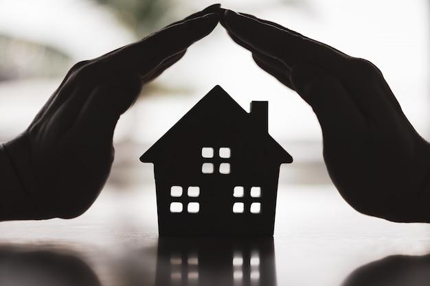 Sylwetka ciężki papierowy dom z dwa rękami na stole, symbol dla budowy