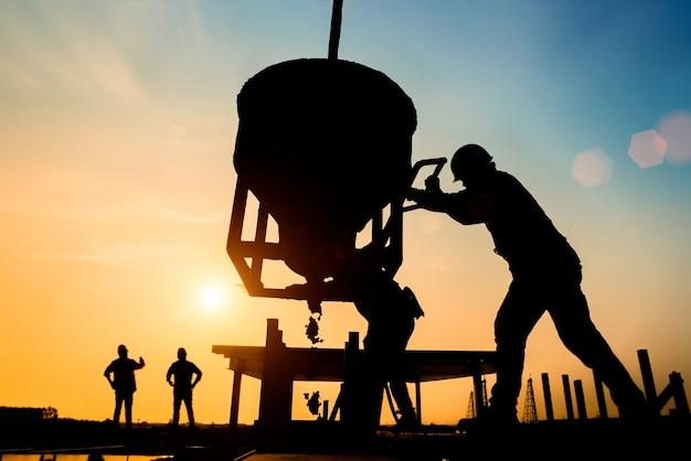 Sylwetka cywilny inżynier i pracownik budowlany pracuje na rusztowaniu