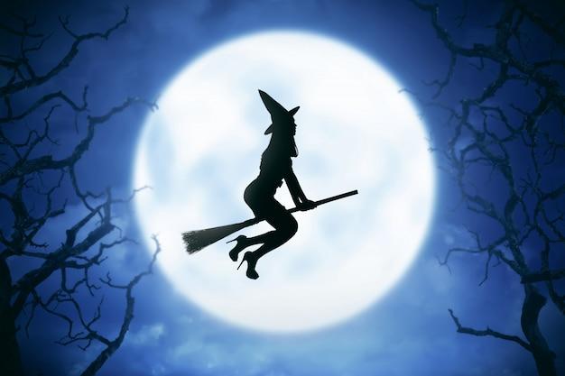 Sylwetka czarownicy kobieta jedzie magiczną miotłę