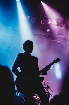 Sylwetka człowieka, gra na gitarze na scenie. ciemne tło, dym, reflektory