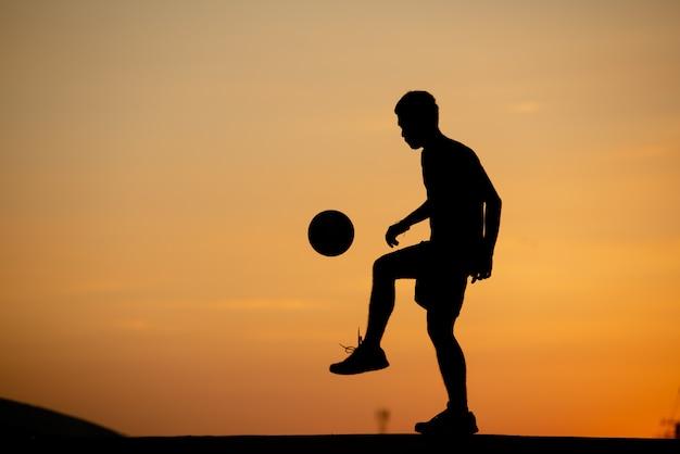 Sylwetka człowieka, gry w piłkę nożną w złotej godzinie, zachód słońca.