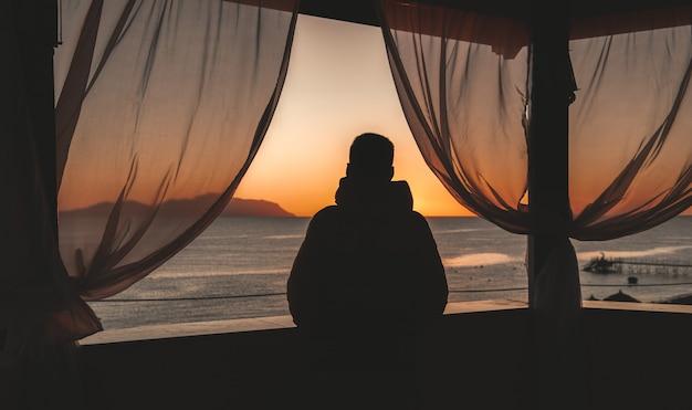 Sylwetka człowieka i widok na morze z altanki
