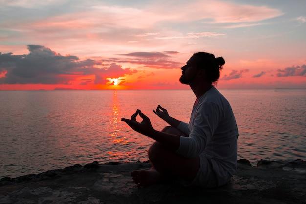 Sylwetka człowieka jogi w tle zachodu słońca.
