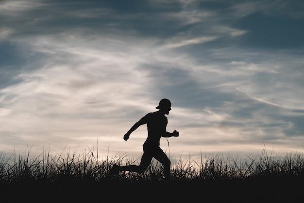 Sylwetka człowieka, który biegnie przez łąkę. pochmurne niebo