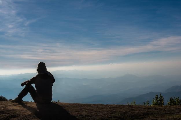 Sylwetka człowieka, który siedzi i patrząc na tle krajobraz gór