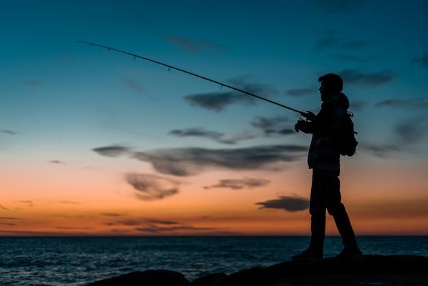 Sylwetka człowieka, łowienie ryb na plaży o zachodzie słońca