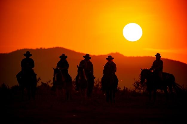 Sylwetka człowieka na koniach przed zachodem słońca nad górą