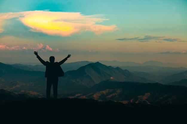 Sylwetka człowieka na szczycie góry na tle nieba i światła słonecznego, biznes, sukces, przywództwo, osiągnięcia i koncepcja ludzi