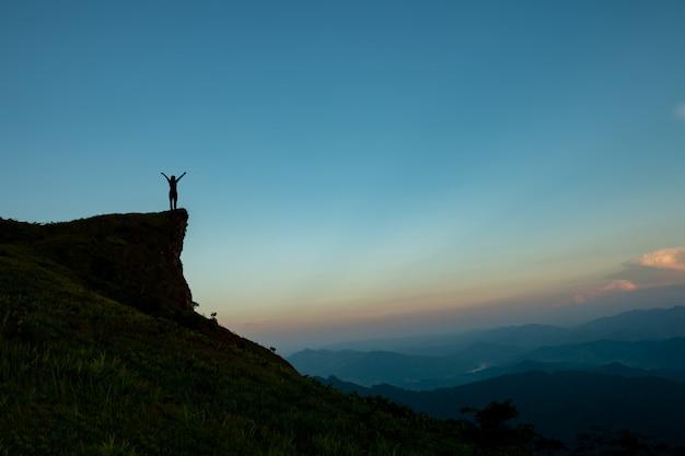 Sylwetka człowieka na szczycie góry nad niebo i słońce jasne tło