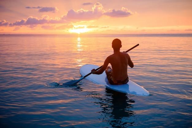 Sylwetka człowieka paddleboarding o zachodzie słońca