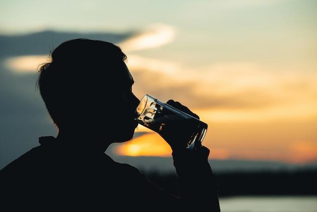 Sylwetka człowieka picie piwa podczas zachodu słońca