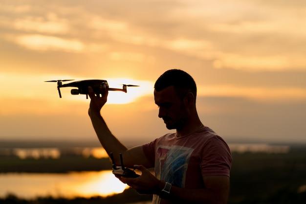 Sylwetka człowieka pilotującego drona o zachodzie słońca ze słonecznym niebem w tle