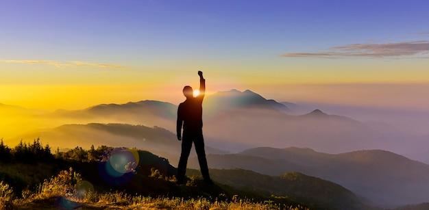 Sylwetka człowieka ręka w górę na pokazie górskim startowa walka cel zmiana wyzwanie koncepcja sukcesu