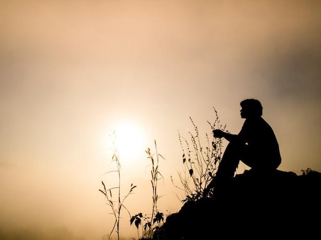Sylwetka człowieka siedzącego na klifie o wschodzie słońca.