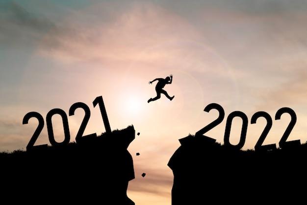 Sylwetka człowieka skaczącego z klifu 2021 do klifu 2022 z chmurnym niebem i światłem słonecznym.