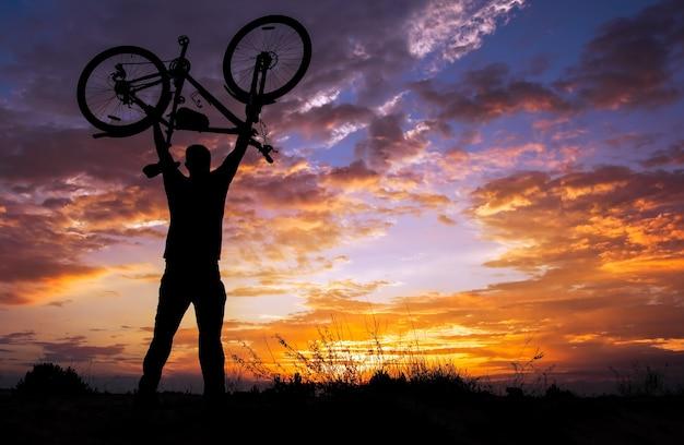 Sylwetka człowieka stanąć w akcji podnoszenia roweru nad głową o zachodzie słońca