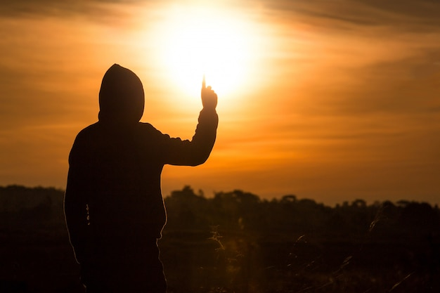 Sylwetka człowieka stojącego i podnieść ręce w powietrzu podczas zachodu słońca
