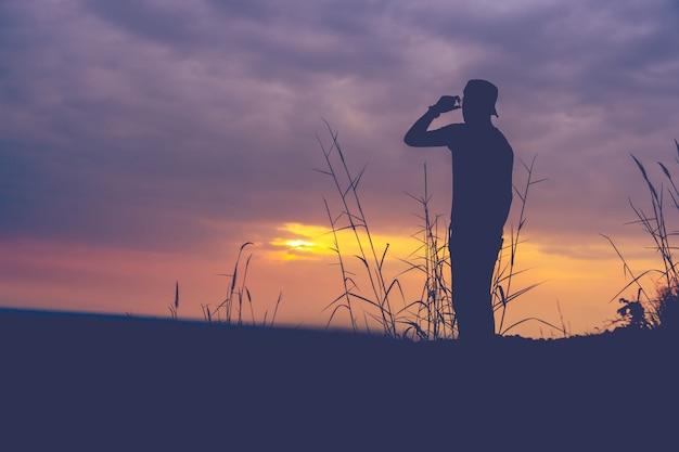 Sylwetka człowieka stojącego na górze o zachodzie słońca