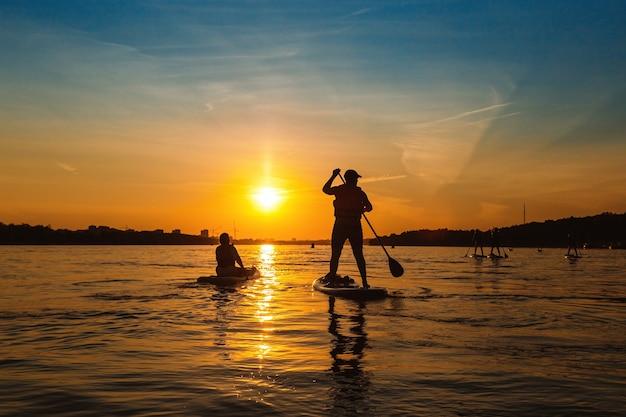 Sylwetka człowieka stojącego na sapboard mężczyzna pływa łodzią po rzece o zachodzie słońca z pięknym widokiem