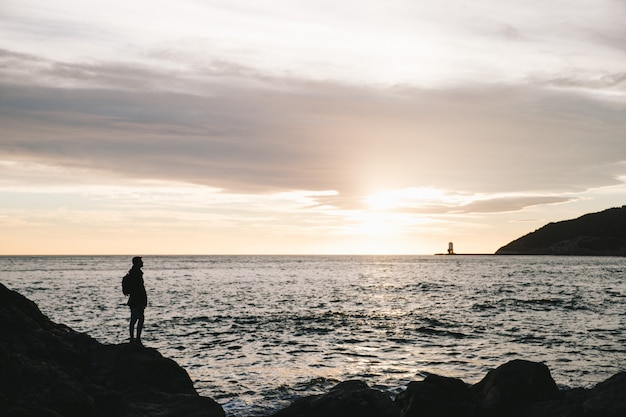 Sylwetka człowieka stojącego w skale na zachód słońca na plaży