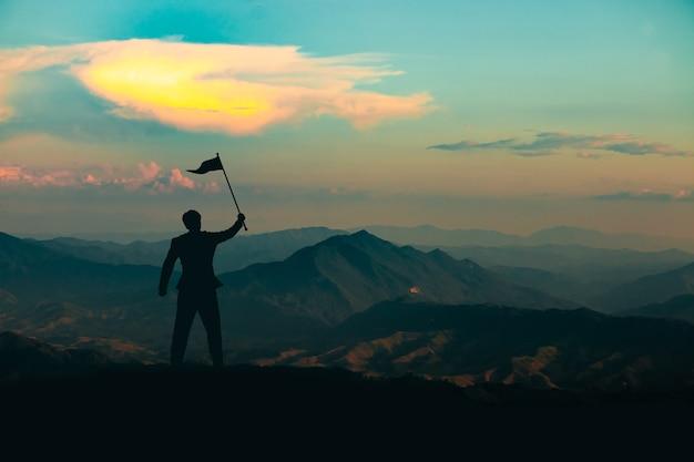 Sylwetka człowieka stojącego z flagą zwycięstwa na szczycie góry na tle nieba wschód słońca, biznes, sukces, przywództwo i koncepcja osiągnięcia