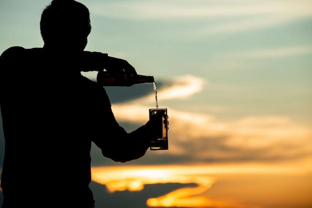 Sylwetka człowieka trzyma piwo podczas zachodu słońca