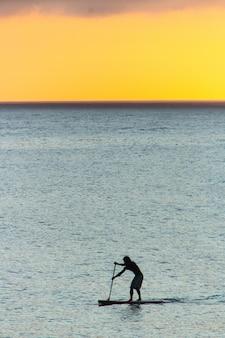 Sylwetka człowieka z jego wiosła wstać z pięknym zachodem słońca