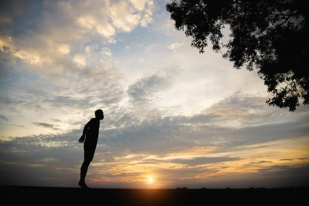 Sylwetka człowieka z mężczyzną ćwiczenia w zachodzie słońca.