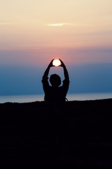 Sylwetka człowieka z obiema rękami nad głową śledzącego słońce podczas złotej godziny