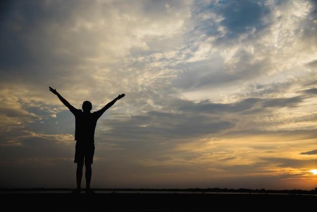 Sylwetka człowieka z podniesionymi rękami o zachodzie słońca.