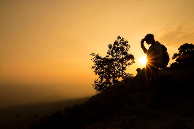 Sylwetka człowieka zrelaksować się na klifie i góry z zachodem słońca w godzinach wieczornych