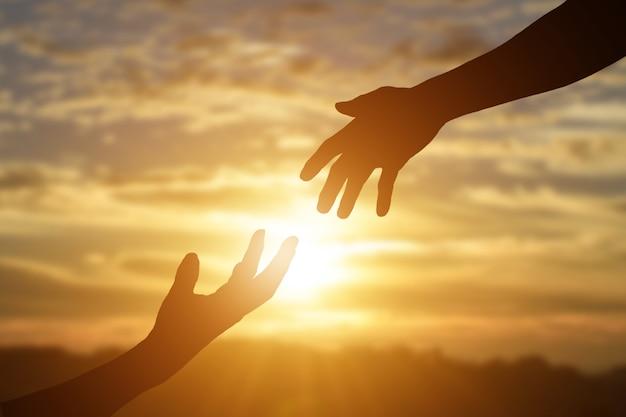 Sylwetka dając pomocną dłoń, nadzieję i wspierać siebie na tle zachodu słońca