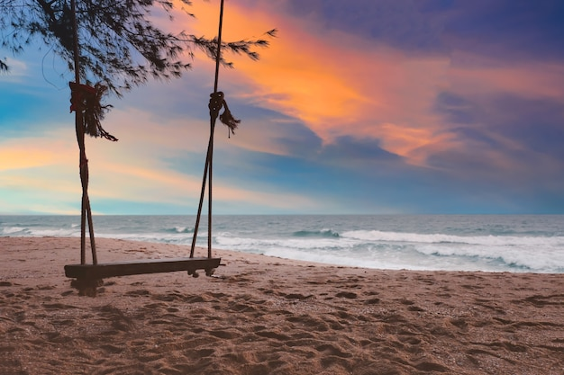 Sylwetka drewniana huśtawka na plaży o zachodzie słońca na kolorowe niebo