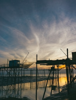 Sylwetka drewniane stojaki w pobliżu morza podczas zachodu słońca
