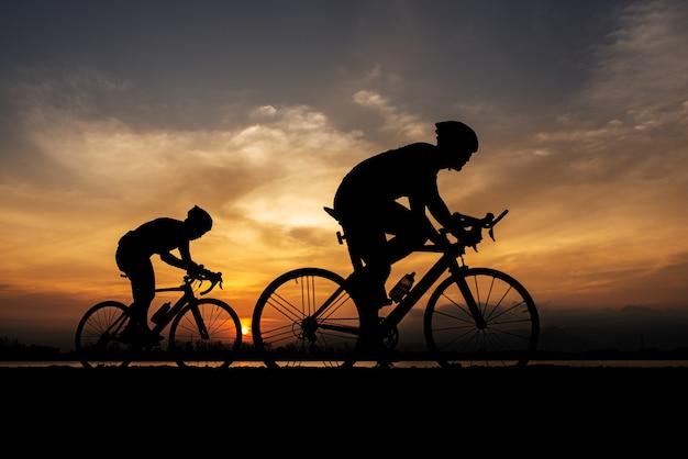 Sylwetka dwa rower szosowy rowerzysta człowiek na rowerze w godzinach porannych.