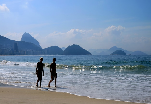 Sylwetka dwóch młoda dziewczyna spaceru na słonecznej plaży