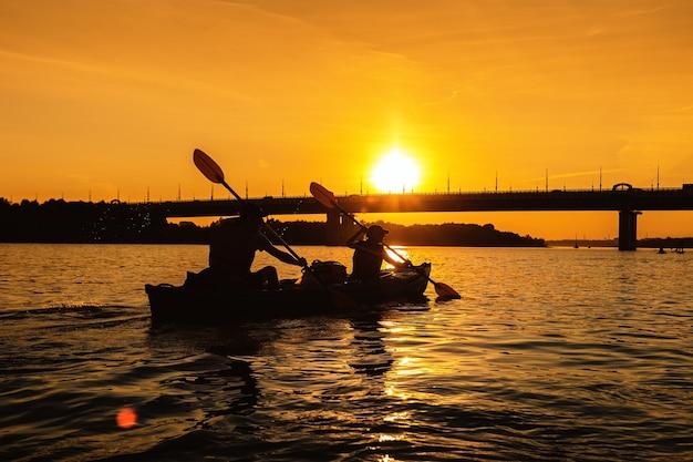 Sylwetka dwóch osób pływających kajakiem po miejskiej rzece o zachodzie słońca mała lokalna podróż z rodziną lub przyjacielem