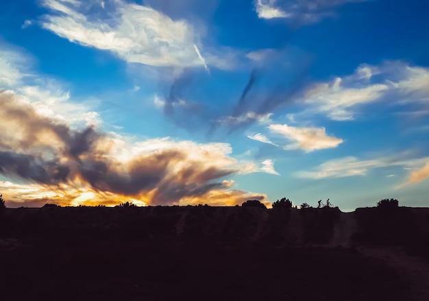 Sylwetka dwóch rowerzystów w dół wzgórza podczas pięknego zachodu słońca.