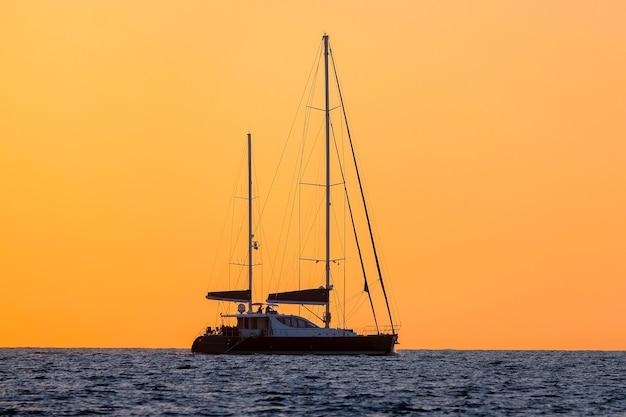 Sylwetka dwumasztowego jachtu na morzu na tle pomarańczowego nieba.