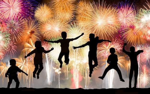 Sylwetka dzieci skaczących nad kolorowymi fajerwerkami