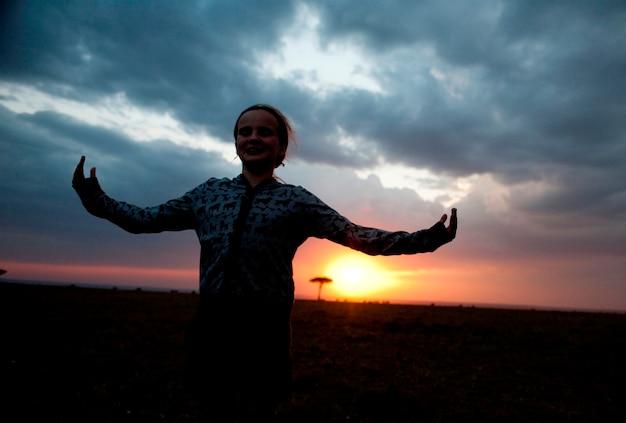 Sylwetka dziewczyna przeciw kenii niebu przy zmierzchem
