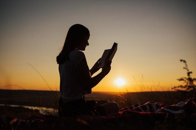 Sylwetka dziewczyny czytać książkę o zachodzie słońca. turysta młoda kobieta siedzi na trawie i czyta książkę o zachodzie słońca w górach.