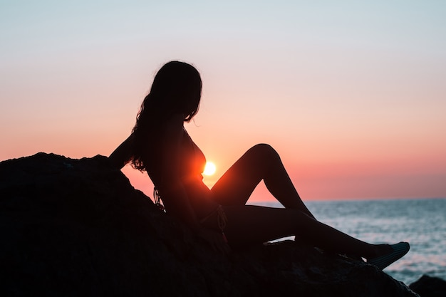 Sylwetka dziewczyny na plaży podczas wschodu słońca