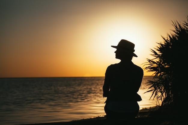 Sylwetka dziewczyny nad brzegiem morza, podziwiając zachód słońca