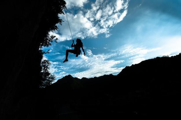 Sylwetka dziewczyny schodzącej z liny po wspinaczce
