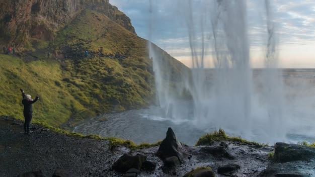 Sylwetka dziewczyny stoi za wodospadem o wschodzie słońca w seljalandsfoss islandia