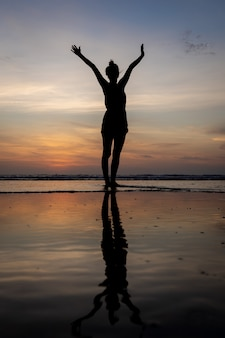 Sylwetka dziewczyny stojącej w wodzie z podniesionymi rękami